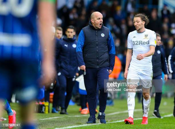 Wigan Athletic manager Paul Cook has words with Leeds United's Luke Ayling at the half time break during the Sky Bet Championship match between Leeds...