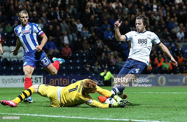 Wigan Athletic's Adam Bogdan dives at the feet of Preston North End's Ben Pearson during the Sky Bet Championship match between Preston North End and...