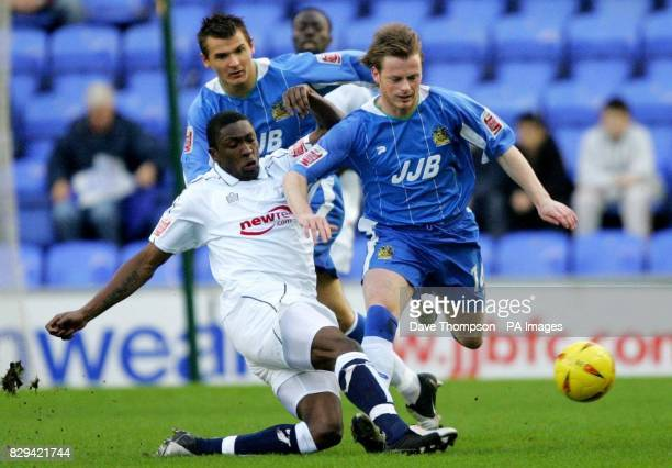 Wigan Athletic's Alan Mahon is tackled by Preston North End's Dickson Etuhu during the CocaCola Championship match at the JJB Stadium THIS PICTURE...