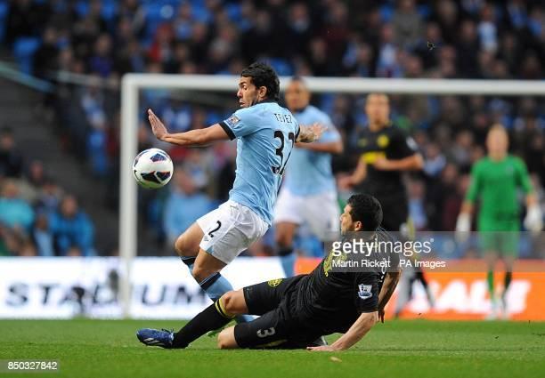 Wigan Athletic's Antolin Alcaraz slides in on Manchester City's Carlos Tevez