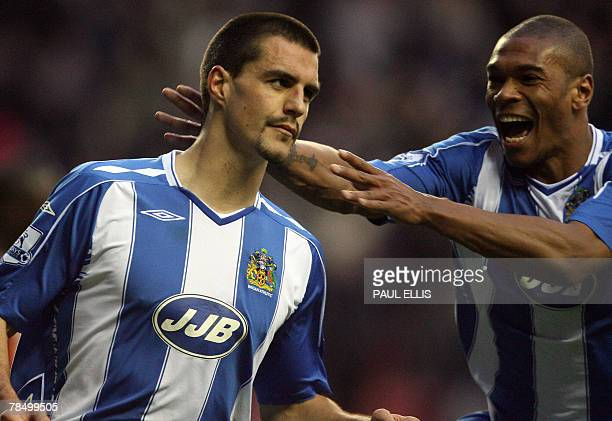Wigan Athletic's Austrian midfielder Paul Scharner is congratulated by English forward Marcus Bent after scoring the third goal against Blackburn...