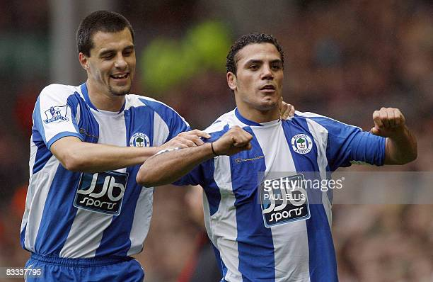 Wigan Athletic's Egyptian forward Amr Zaki is congratulated by teammate Austrian midfielder Paul Scharner after scoring against Liverpool during...