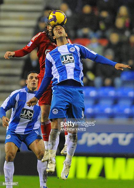 Wigan Athletic's Egyptian forward Mido wins a header from Liverpool's Brazilian midfielder Lucas during the English Premier league football match at...