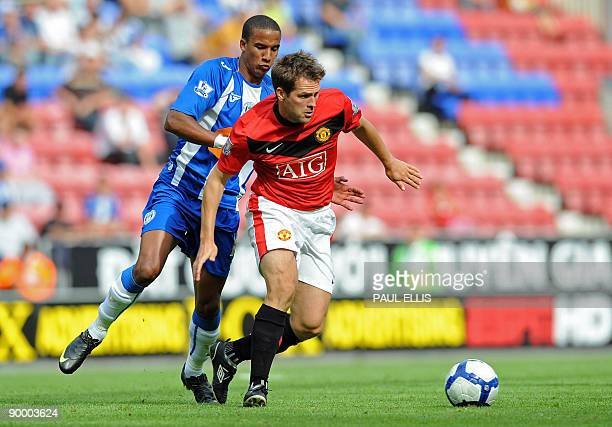 Wigan Athletic's English forward Scott Sinclair competes for the ball with Manchester United's English forward Michael Owen during the English...