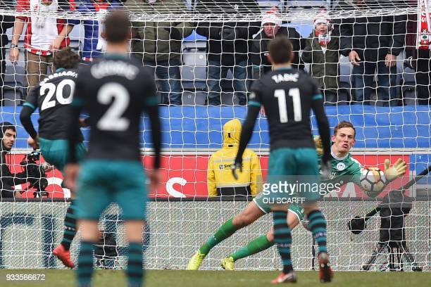 Wigan Athletic's English goalkeeper Christian Walton makes a diving save from a penalty kick taken by Southampton's Italian striker Manolo Gabbiadini...