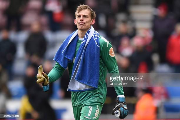 Wigan Athletic's English goalkeeper Christian Walton reacts to their defeat on the pitch after the English FA Cup quarterfinal football match between...