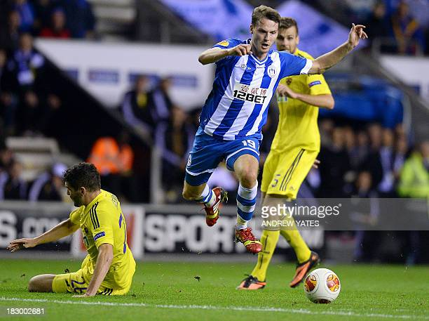 Wigan Athletic's English midfielder Nick Powell avoids a challenge from NK Maribor's Slovenian defender Aleksander Rajcevic during the UEFA Europa...