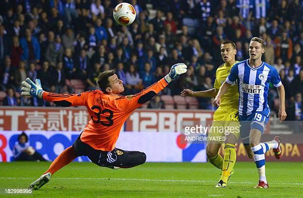 Wigan Athletic's English midfielder Nick Powell has his shot saved by NK Maribor's Slovenian goalkeeper Jasmin Handanovic during the UEFA Europa...