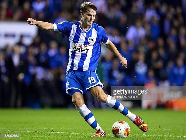 Wigan Athletic's English midfielder Nick Powell shoots to score his team's third goal during the UEFA Europa League group D football match between...