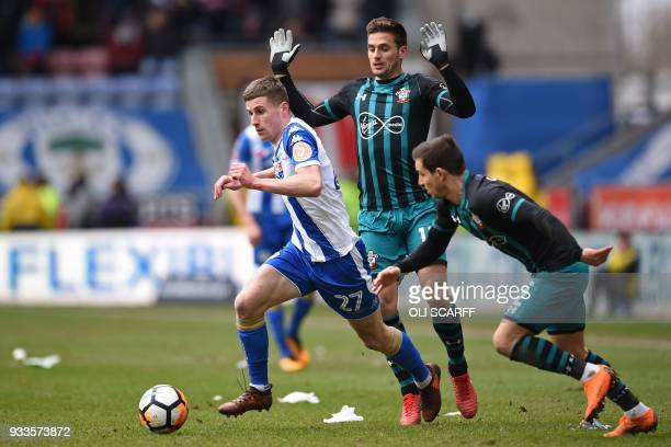 Wigan Athletic's English striker Ryan Colclough runs away from Southampton's Serbian midfielder Dusan Tadic and Southampton's Germanborn Portuguese...