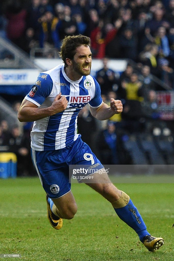 Wigan Athletic's English-born Northern Irish striker Will Grigg celebrates after scoring their second goal from the penalty spot during the English FA Cup fourth round football match between Wigan Athletic and West Ham United at the DW Stadium in Wigan, northwest England, on January 27, 2018. / AFP PHOTO / Oli SCARFF / RESTRICTED TO EDITORIAL USE. No use with unauthorized audio, video, data, fixture lists, club/league logos or 'live' services. Online in-match use limited to 75 images, no video emulation. No use in betting, games or single club/league/player publications. /