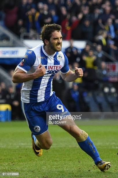 Wigan Athletic's Englishborn Northern Irish striker Will Grigg celebrates after scoring their second goal from the penalty spot during the English FA...