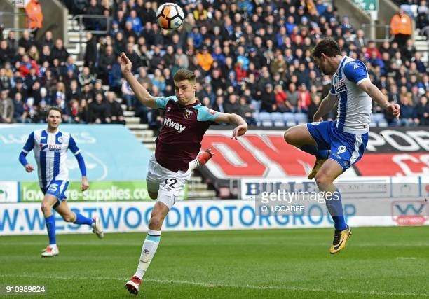 Wigan Athletic's Englishborn Northern Irish striker Will Grigg jumps to head past West Ham United's English defender Reece Burke for the opening goal...