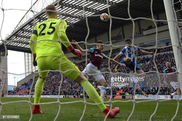 Wigan Athletic's Englishborn Northern Irish striker Will Grigg jumps to head the opening goal past West Ham United's English goalkeeper Joe Hart...