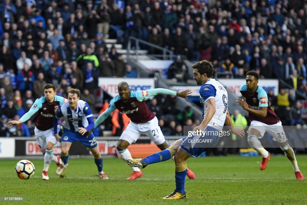 Wigan Athletic's English-born Northern Irish striker Will Grigg (2nd R) scores their second goal from the penalty spot during the English FA Cup fourth round football match between Wigan Athletic and West Ham United at the DW Stadium in Wigan, northwest England, on January 27, 2018. / AFP PHOTO / Oli SCARFF / RESTRICTED TO EDITORIAL USE. No use with unauthorized audio, video, data, fixture lists, club/league logos or 'live' services. Online in-match use limited to 75 images, no video emulation. No use in betting, games or single club/league/player publications. /