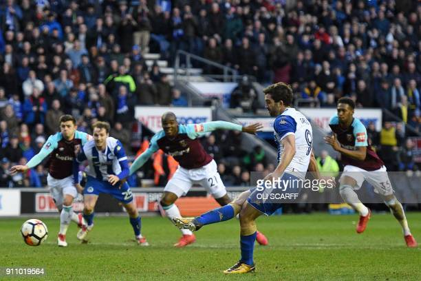 Wigan Athletic's Englishborn Northern Irish striker Will Grigg scores their second goal from the penalty spot during the English FA Cup fourth round...