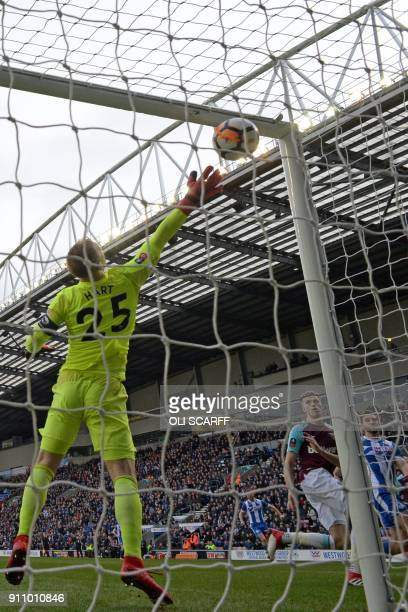 Wigan Athletic's Englishborn Northern Irish striker Will Grigg watches as his header beats West Ham United's English goalkeeper Joe Hart for the...