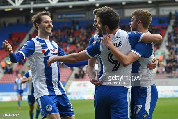 Wigan Athletic's English-born Northern Irish striker Will Grigg celebrates with teammates after scoring the opening goal of the English FA Cup fourth...