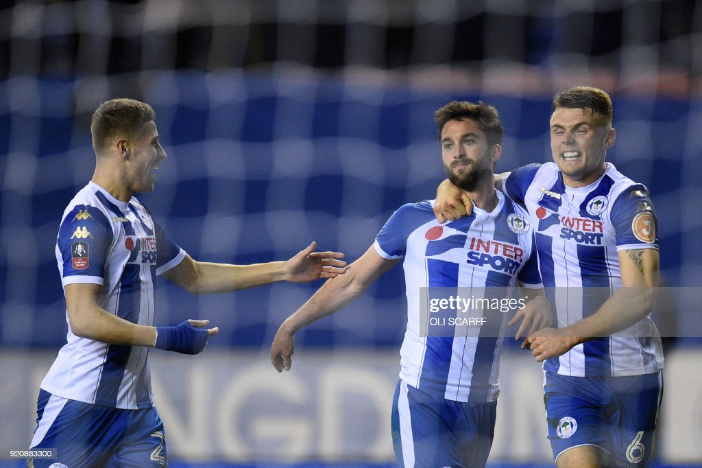 Wigan Athletic's English-born Northern Irish striker Will Grigg (C) celebrates with teammates scoring his team's first goal during the English FA Cup fifth round football match between Wigan Athletic and Manchester City at the DW Stadium in Wigan, northwest England, on February 19, 2018. / AFP PHOTO / Oli SCARFF / RESTRICTED TO EDITORIAL USE. No use with unauthorized audio, video, data, fixture lists, club/league logos or 'live' services. Online in-match use limited to 75 images, no video emulation. No use in betting, games or single club/league/player publications. /