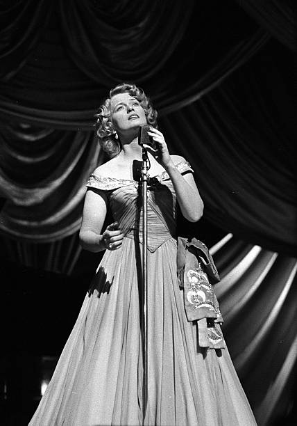"""Wigan, England. 1954. Popular British singing star Joan Regan, known best from the television programme """"Quite Contrary"""", is pictured during her act at the Hippodrome Theatre."""
