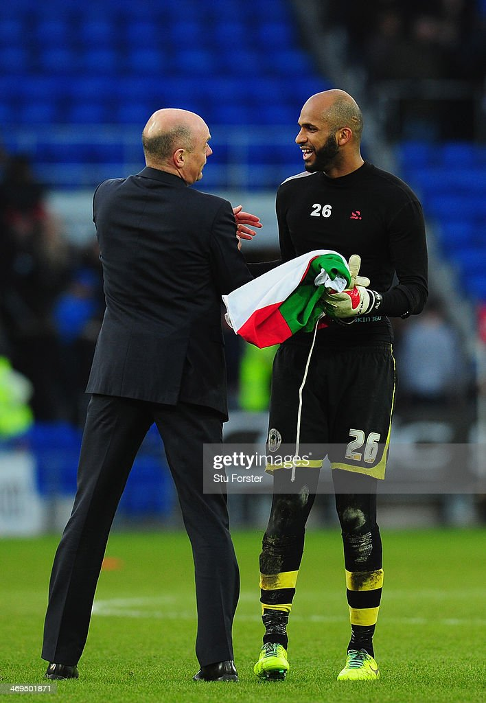 Wigan goalkeeper Ali Al-Habsi celebrates with manager Uwe Rosler after the FA Cup Fifth Round match between Cardiff City and Wigan Athletic at Cardiff City Stadium on February 15, 2014 in Cardiff, Wales.