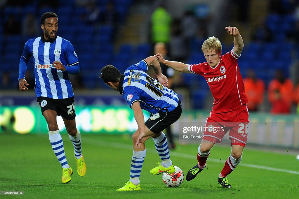 Wigan player Don Cowie (c) challenges Mats Daehli of Cardiff (r) during the Sky Bet Championship match between Cardiff City and Wigan Athletic at Cardiff City Stadium on August 19, 2014 in Cardiff, Wales.