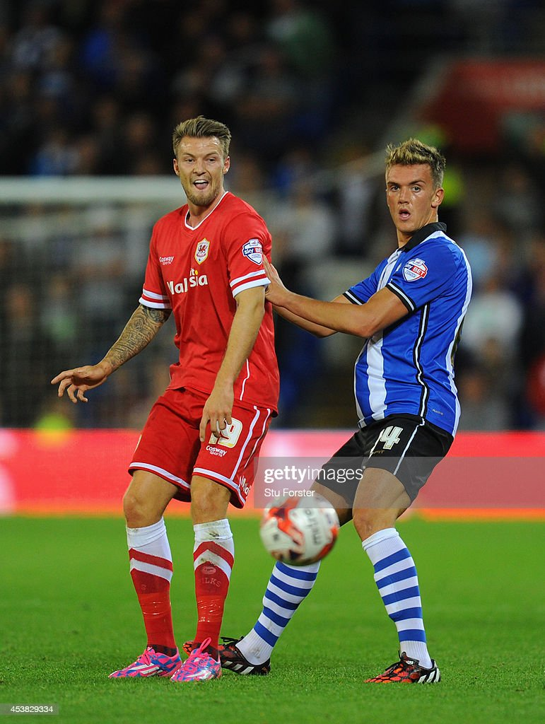 Wigan player Emyr Hughes (r) challenges Anthony Pilkington of Cardiff during the Sky Bet Championship match between Cardiff City and Wigan Athletic at Cardiff City Stadium on August 19, 2014 in Cardiff, Wales.