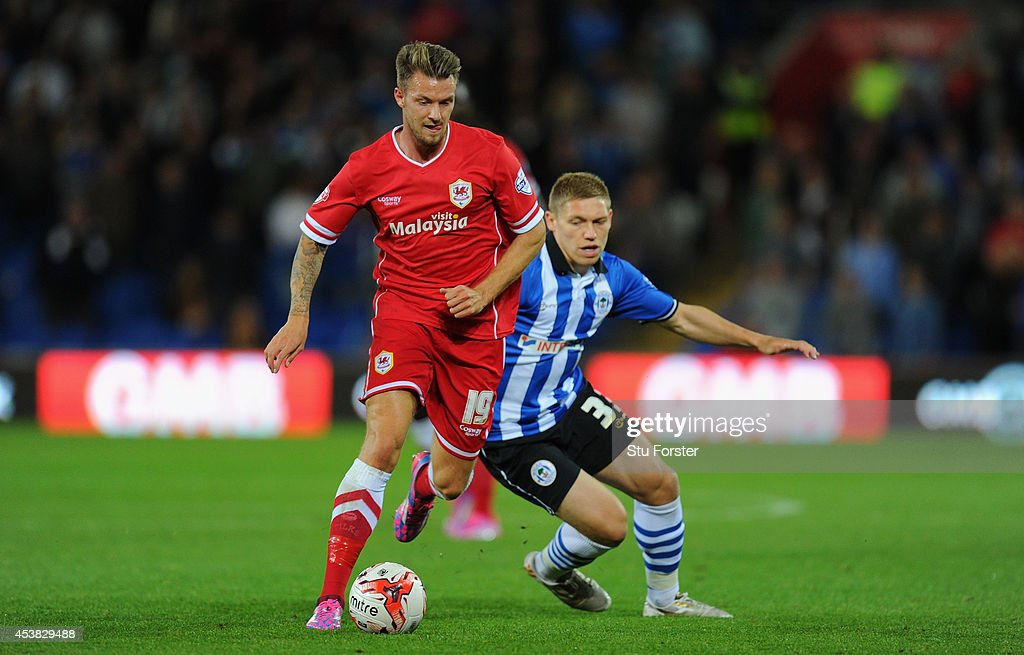 Wigan player Martyn Waghorn (r) challenges Anthony Pilkington of Cardiff during the Sky Bet Championship match between Cardiff City and Wigan Athletic at Cardiff City Stadium on August 19, 2014 in Cardiff, Wales.