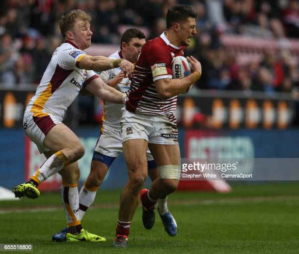 Wigan Warriors' Anthony Gelling is tackled by Huddersfield Giants' Danny Brough and Aaron Murphy during the Betfred Super League Round 5 match...