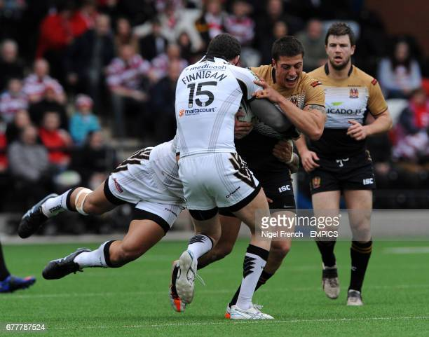 Wigan Warriors' Anthony Gelling is tackled by Widnes Vikings' Simon Finnigan and Frank Winterstein