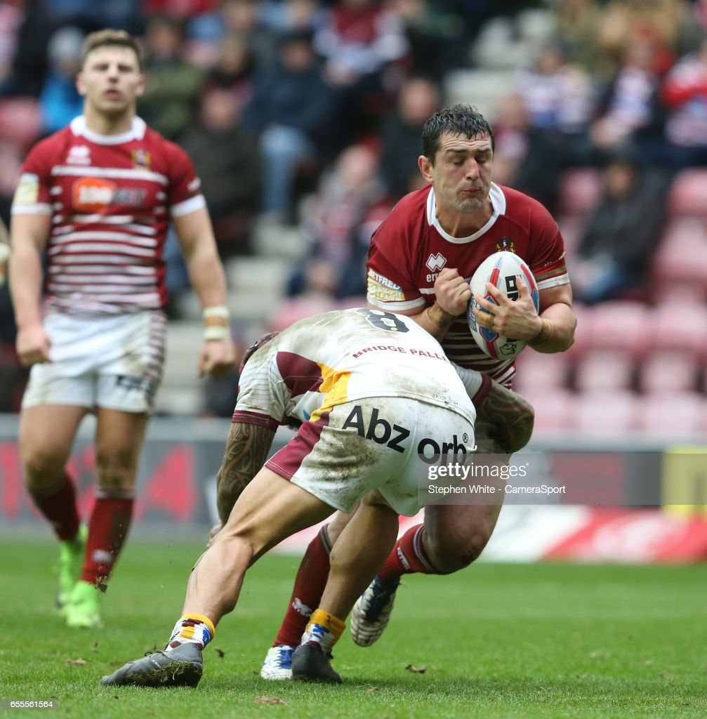 Wigan Warriors' Ben Flower is tackled by Huddersfield Giants' Sam Rapira during the Betfred Super League Round 5 match between Wigan Warriors and Huddersfield Giants at DW Stadium on March 19, 2017 in Wigan, England.