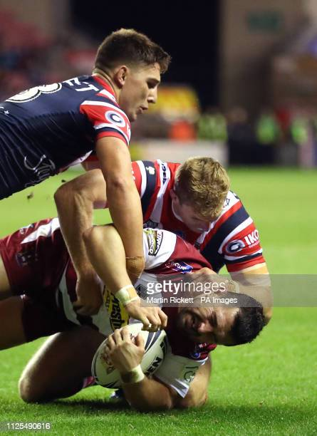 Wigan Warriors' Ben Flower is tackled by Sydney Roosters' Mitchell Aubusson and Sydney Roosters' Victor Radley during the World Club Challenge match...