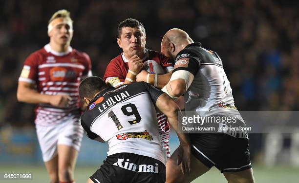 Wigan Warriors' Ben Flower is tackled by Widnes Vikings' Macgraff Leuluai and Gil Dudson during the Betfred Super League Round 2 match between Widnes...