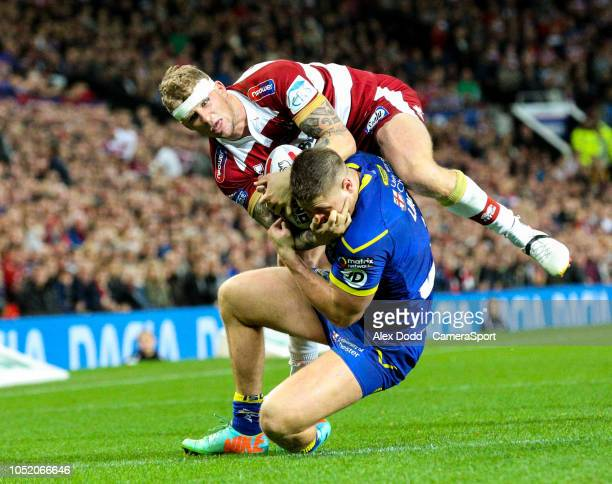 Wigan Warriors' Dominic Manfredi competes with Warrington Wolves 's Tom Lineham for the ball during the Betfred Super League Grand Final match...