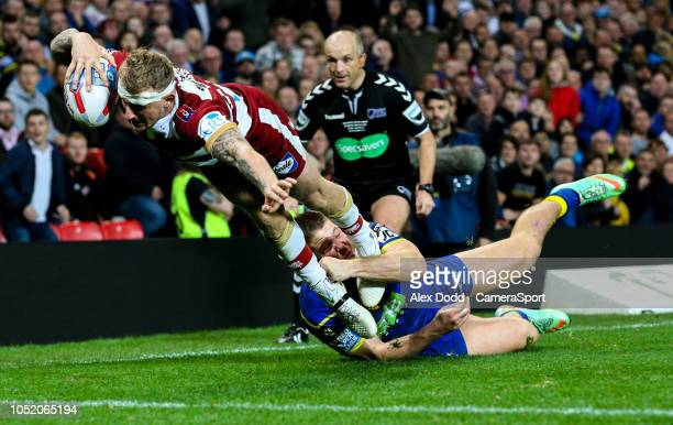 Wigan Warriors' Dominic Manfredi goes over to score his side's third try under pressure from Warrington Wolves 's Tom Lineham during the Betfred...