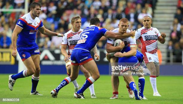 Wigan Warriors' Jack Hughes is tackled by St Helens' Mark Flanagan during the First Utility Super League at the DW Stadium Wigan
