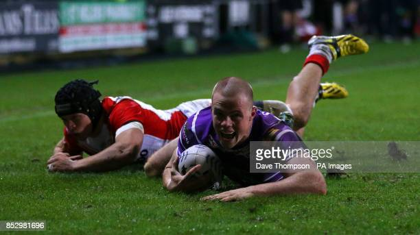 Wigan Warriors Joe Burgess crosses the try line to score during James Roby's Testimonial match at Langtree Park St Helens