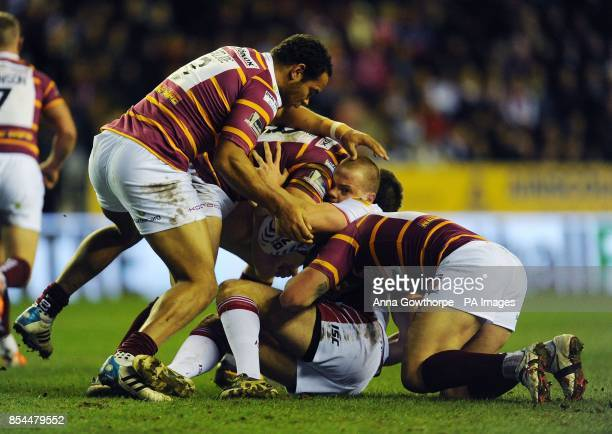 Wigan Warriors' Joe Burgess is tackled by Huddersfield Giants' Leroy Cudjoe Chris Bailey and Shaun Lunt during the First Utility Super League match...