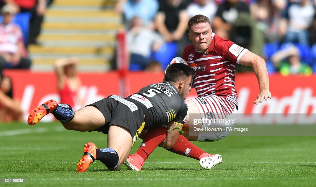 Wigan Warriors' Joe Burgess is tackled by Salford Red Devils' Niall Evalds during the Challenge Cup Semi Final match at The Halliwell Jones Stadium, Warrington.