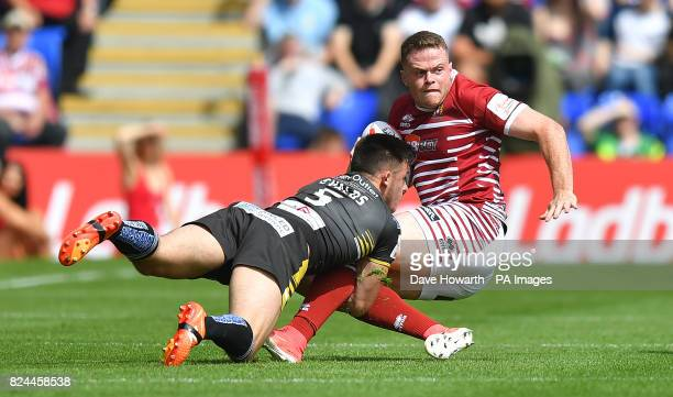 Wigan Warriors' Joe Burgess is tackled by Salford Red Devils' Niall Evalds during the Challenge Cup Semi Final match at The Halliwell Jones Stadium...