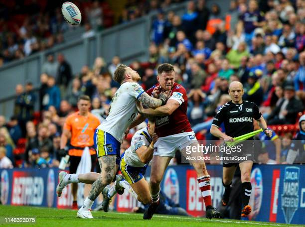 Wigan Warriors' Joe Burgess passes the ball infield as he's tackled by Warrington Wolves' Josh Charnley during the Dacia Magic Weekend Round 16 match...