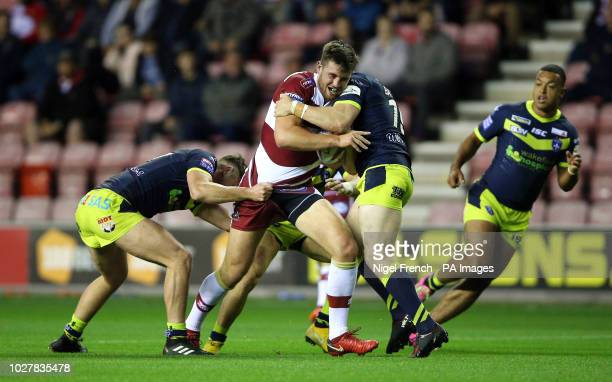Wigan Warriors' Joe Green Wood is tackled by Wakefield Trinity's Jordan Crowther and James Batchelor during the Betfred Super League Super 8's match...