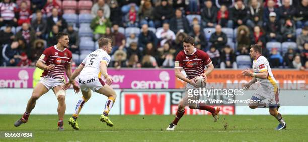 Wigan Warriors' Joel Tomkins watched by Huddersfield Giants' Danny Brough and Aaron Murphy during the Betfred Super League Round 5 match between...