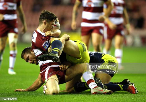 Wigan Warriors' John Bateman is tackled by Wakefield Trinity's Tyler Randell during the Betfred Super League Super 8's match at the DW Stadium Wigan