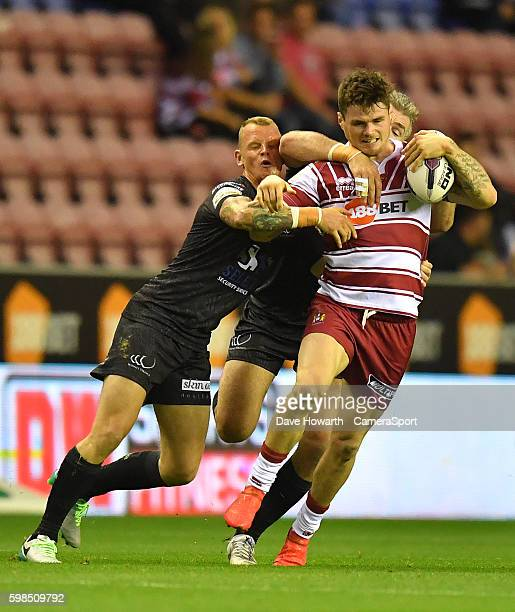 Wigan Warriors' John Bateman is tackled by Widnes Vikings' Chris Houston and Kevin Brown during the First Utility Super League Super 8s Round 4 match...