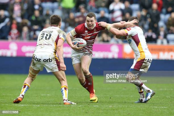 Wigan Warriors' Liam Marshall is tackled by Huddersfield Giants' Alex Mellor and Danny Brough during the Betfred Super League Round 5 match between...