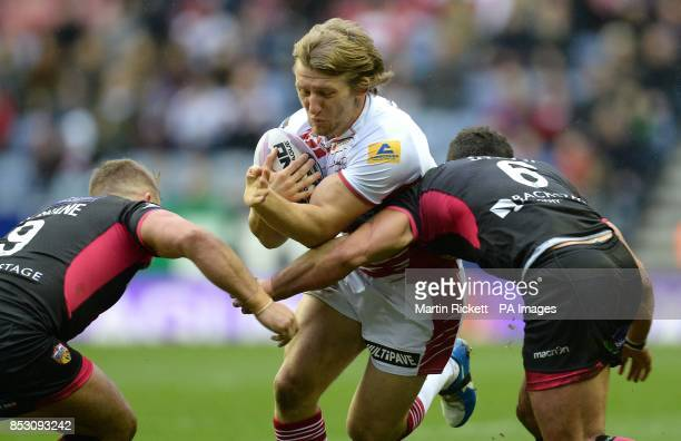 Wigan Warriors Logan Tomkins is tackled by Wakefield Trinity Wildcats' Paul McShane and Paul Sykes during the First Utility Super League match at the...
