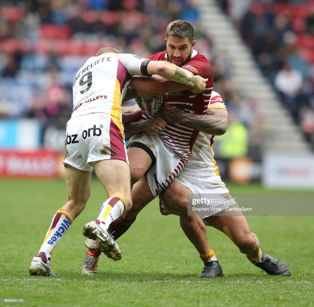 Wigan Warriors' Romain Navarrete is tackled by Huddersfield Giants' Ryan Hinchcliffe (left) and Sam Rapira during the Betfred Super League Round 5 match between Wigan Warriors and Huddersfield Giants at DW Stadium on March 19, 2017 in Wigan, England.