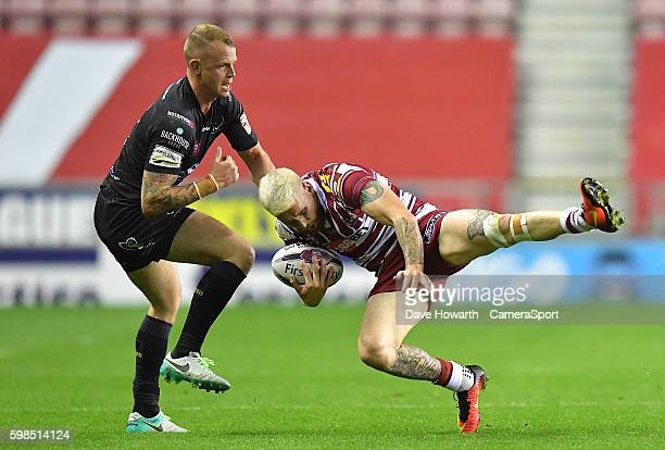 Wigan Warriors' Sam Tomkins is tackled by Widnes Vikings' Kevin Brown during the First Utility Super League Super 8s Round 4 match between Wigan...