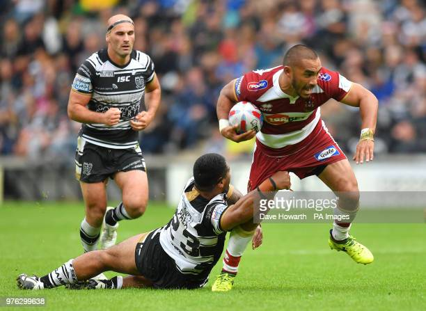 Wigan Warriors' Thomas Leuluai is tackled by Hull FC's Mickey Paea during the Betfred Super League match at the KCOM Stadium Hull